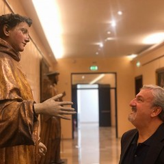 Il presidente Emiliano davanti a una statua lignea