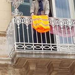 Il sindaco espone un gilet arancioni dal balcone del comune