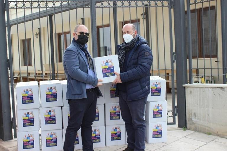 Don Vito Piccinonna riceve i pacchi alimentari per la Caritas