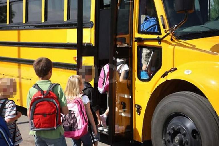 Bambini in attesa di salire su uno scuolabus